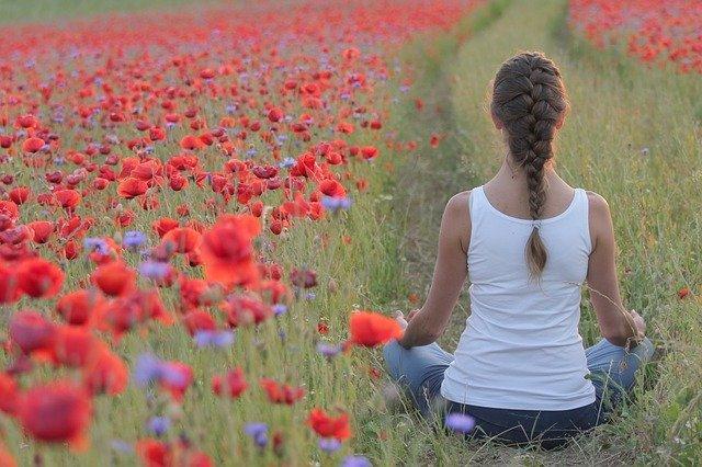 Frau im Feld beim Meditieren