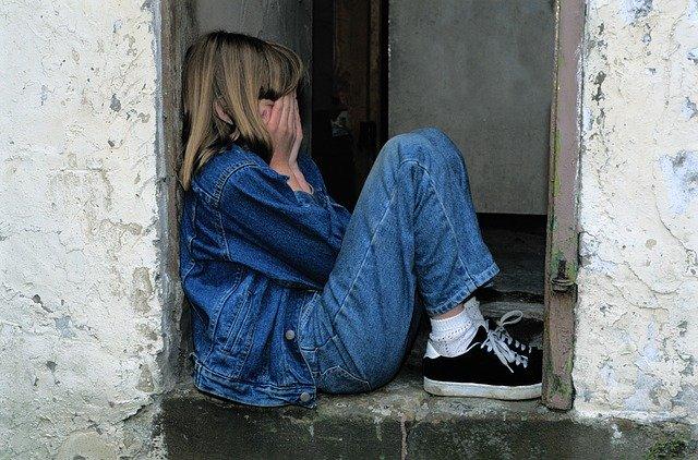 Mädchen sitzt mit Händen vor dem Gesicht am Boden